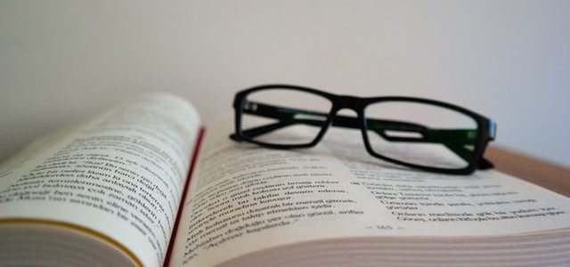 eye glasses resting on an opened book